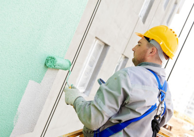24236652 - builder worker painting facade of high-rise building with roller